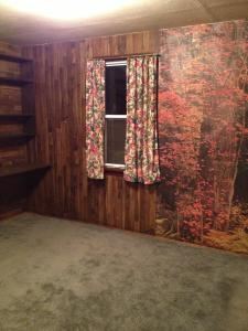 Bedroom 2 with wood paneling, forest wallpaper and wood shelving